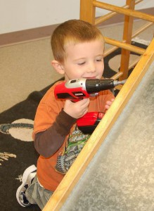 boy uses a toy drill