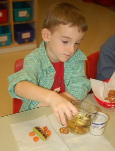 boy pouring juice at snacktime