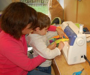 teacher helps boy use sewing machine