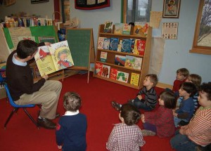 a dad reads a book to a group of children