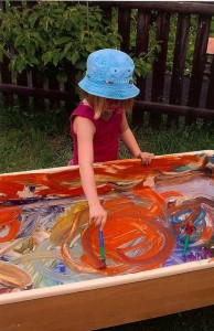 girl paints outdoors