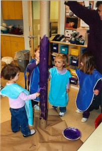 kids wearing smocks paint tall pole blue