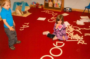 kids make letters out of wooden shapes on the floor